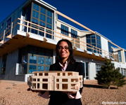 Mixed race architect holding building model with building in the background against a dark blue sky. She has her hair pulled back and is smiling at the camera.